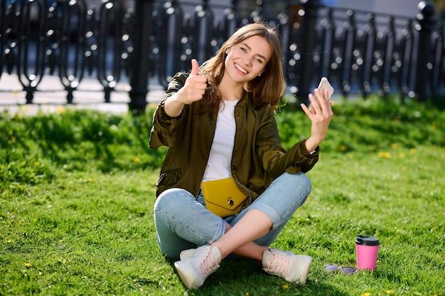 웃는 매력적인 젊은 여자는 잔디에 앉아 공공 공원에서 이완 스마트 폰을 사용하고 제스처를 엄지 손가락을 보여줍니다