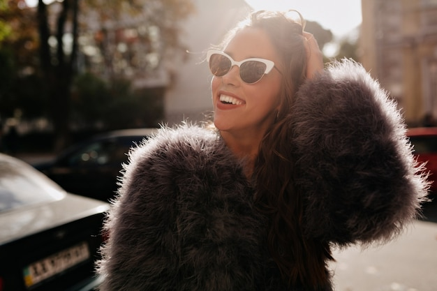 Smiling attractive young woman with dark hairstyle wearing fur coat and stylish glasses smiling