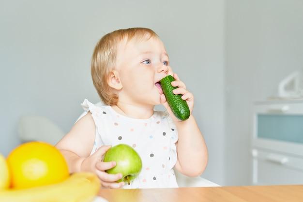 Улыбающийся ребенок, кусающий огурец и держащий зеленое яблоко, сидя на детском стульчике и глядя в сторону