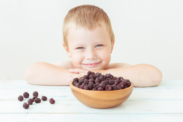 笑みを浮かべて男の子とテーブルの上の熟したブラックベリーのプレート