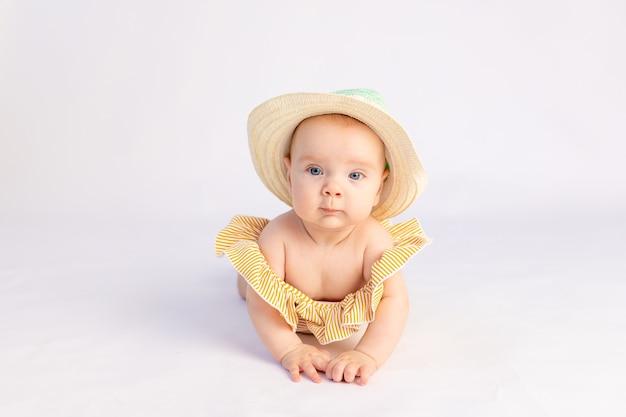白い孤立した背景、テキストのためのスペースに横たわっている水着と太陽の帽子で生後6ヶ月の笑顔の女の赤ちゃん
