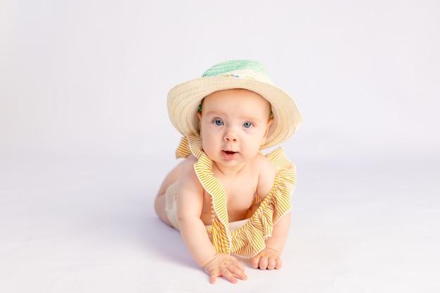 Улыбающаяся девочка 6 месяцев в купальнике и шляпе от солнца лежа
