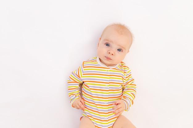 Улыбающаяся девочка 6 месяцев лежала в ярком боди, вид сверху.
