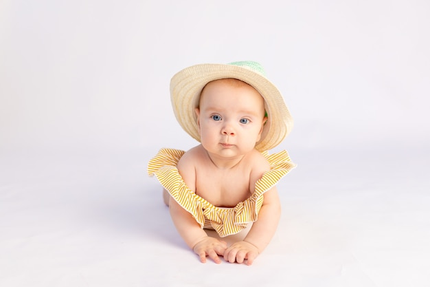 Smiling baby girl 6 months old in a swimsuit and sun hat lying on a white isolated background, space for text