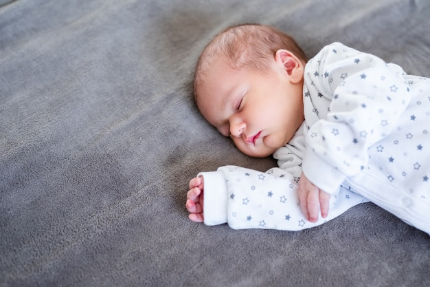 Улыбающаяся девочка, лежа на кровати, спать на синих простынях.