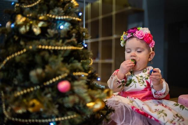 Smiling baby girl near christmas tree