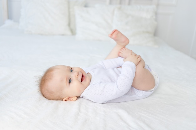 生後6ヶ月の笑顔の女の赤ちゃんは、家の寝室の白い綿のベッドの上で彼女の足を仰向けに寝かせて遊んで笑います