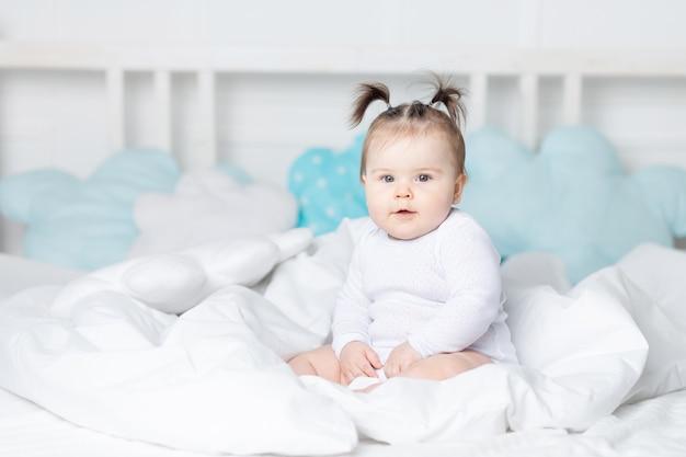 Улыбающийся ребенок в постели на кровати дома, концепция счастливой любящей семьи и детей