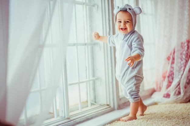 窓に寄りかかって笑顔の赤ちゃん