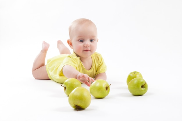 Smiling baby lying on the ground to include apples