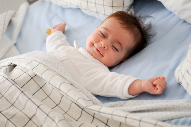 웃는 아기는 침대에 누워