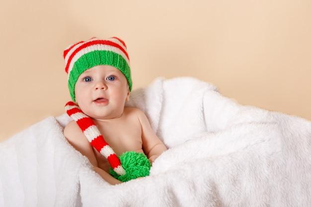 Улыбающийся ребенок, лежащий на белом одеяле в шляпе санта-клауса и костюме