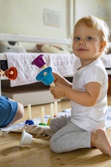 악기 소리 멜로디를 공부하는 색색의 유치한 핸드 벨을 연주 웃는 아기