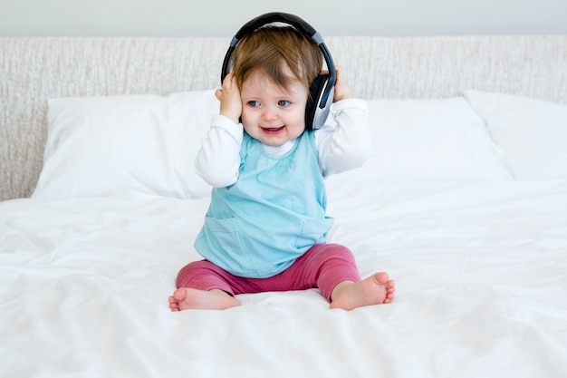 Smiling baby sitting on a bed playing with headphones