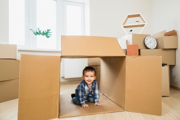 Smiling baby toddler inside an open cardboard box at home