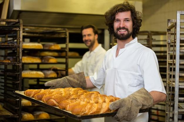 Улыбаясь пекарь несет поднос свежеиспеченного французского багета