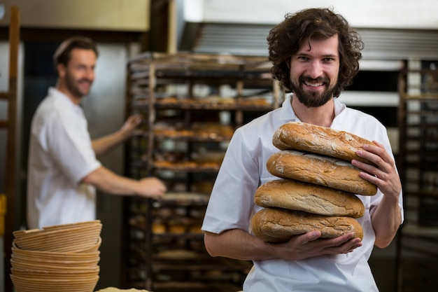 Smiling baker carrying stack of baked breads