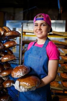 Улыбающаяся девочка пекаря в фартуке, держа хлеб и глядя на камеру. молодая женщина - повар, держащий свежую выпечку. счастливая девушка европейской внешности улыбается пекарне.