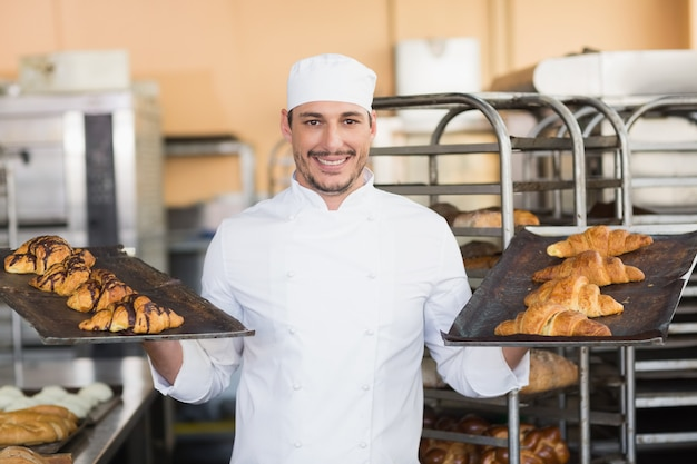 Smiling baker holding trays of croissants