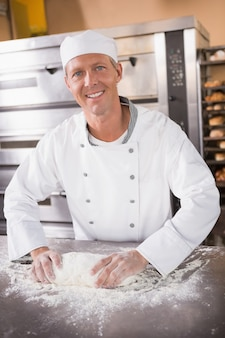Smiling baker kneading dough on counter