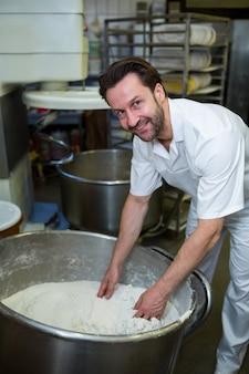 Улыбаясь пекарь смешивания муки