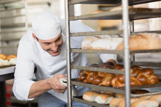 Smiling baker pushing tray of bread