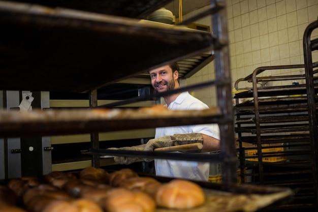 Smiling baker removing baked bun from oven