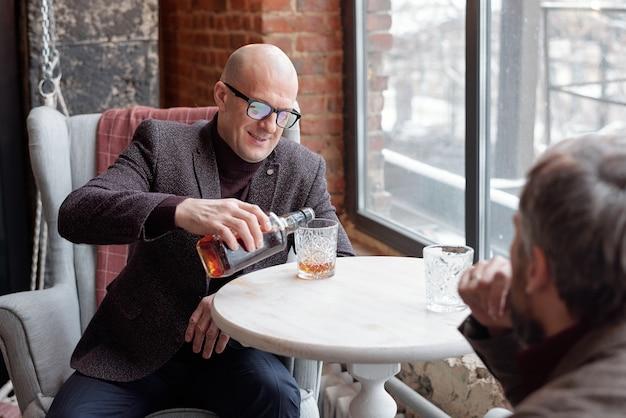 Улыбающийся лысый мужчина в очках сидит за столом и наливает виски в стакан во время встречи с деловым партнером в ресторане