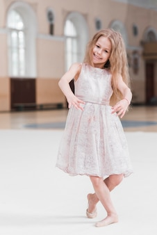 Smiling ballerina girl dancing in dance class