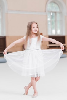 Smiling ballerina girl with crossed leg holding white her dress