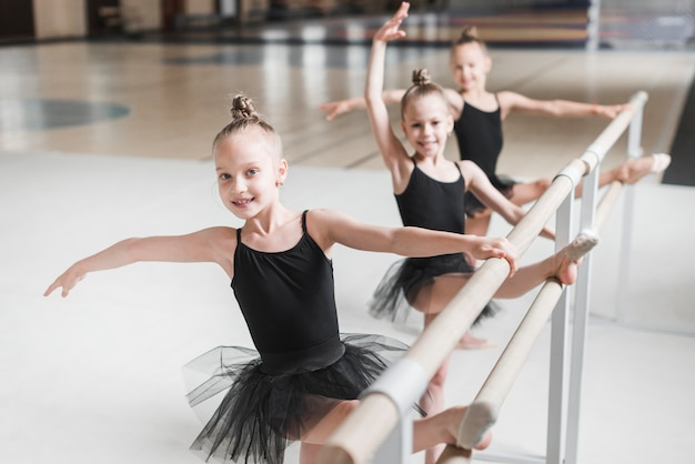 Smiling ballerina girls stretching their legs on barre