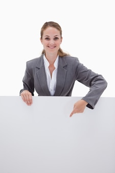 Smiling bank employee pointing down at blank sign against a white background