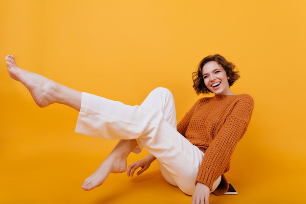 Улыбающаяся босая девушка с экстатическим выражением лица позирует с поднятыми ногами