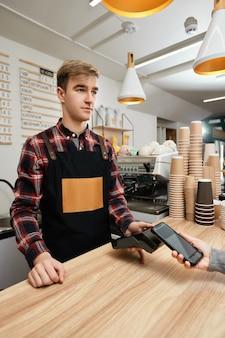 웃는 바리스타는 카페에 있는 포스 머신을 통해 휴대폰으로 결제를 받습니다. nfc 터미널 근처에 전화를 들고 있는 고객은 비접촉식 모바일 결제를 합니다.