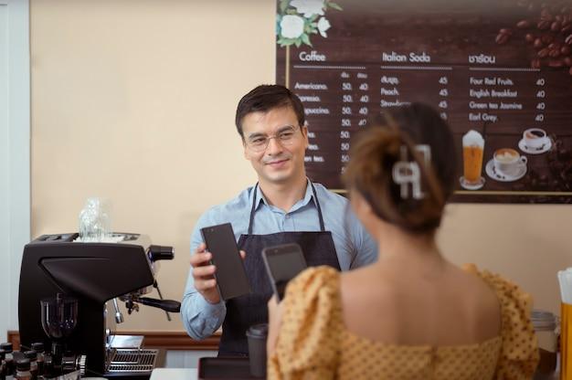 Улыбающийся бариста дает онлайн-платеж покупателю, оплачивает заказ в кафе-магазине