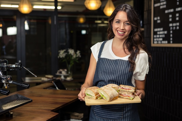 Smiling barista holding plate with sandwich