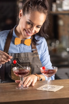 Smiling barmaid wearing wooden bow tie decorates manhattan cocktail drink with a cherry.