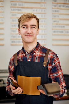 Smiling barman in apron hold modern bank payment terminal in cafe