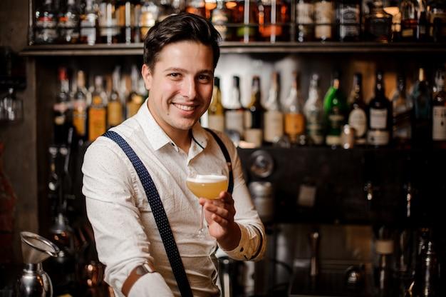 バーのスタンドでカクテルを持って笑顔のバーマン
