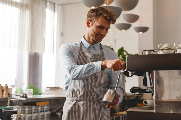 Smiling barman holding silver metallic mug and pouring hot beverage from the tap of coffee machine