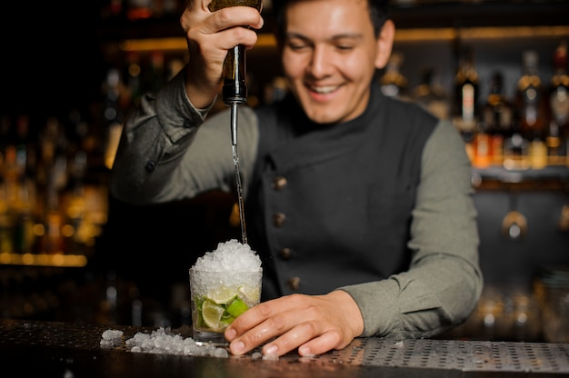 Smiling barman pouring sweet syrup into the mojito