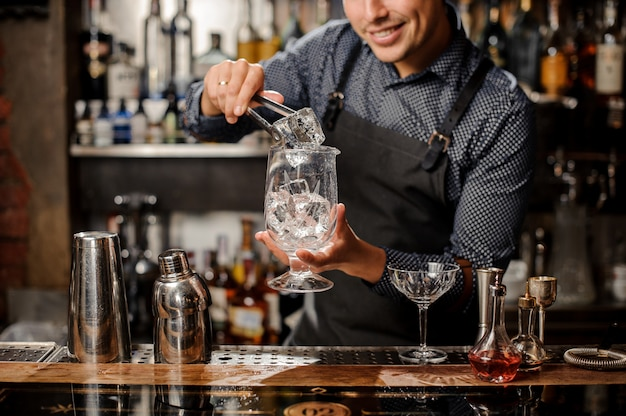 Smiling barman putting a big ice cube with help of special ice tongs