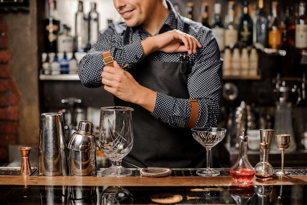 Smiling barman standing behind the bar counter with a bar equipment