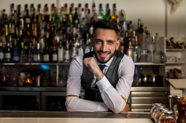 Smiling barman standing at bar counter