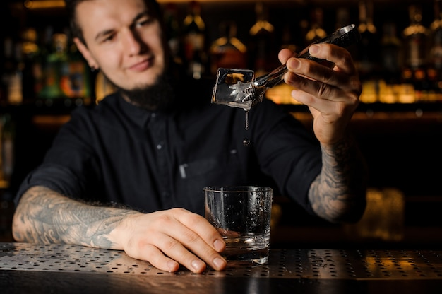 Smiling bartender adding to a drink in the glass a big ice cube with tweezers on the bar counter