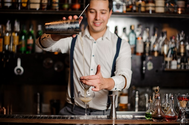 Smiling bartender is making a coctail at the bar stand