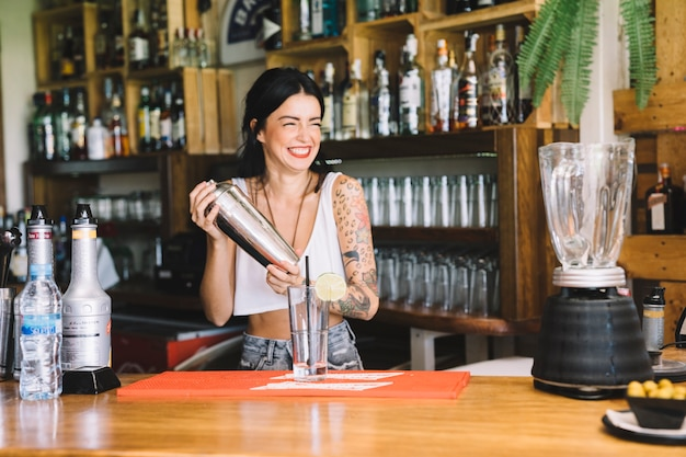 Smiling bartender making cocktail