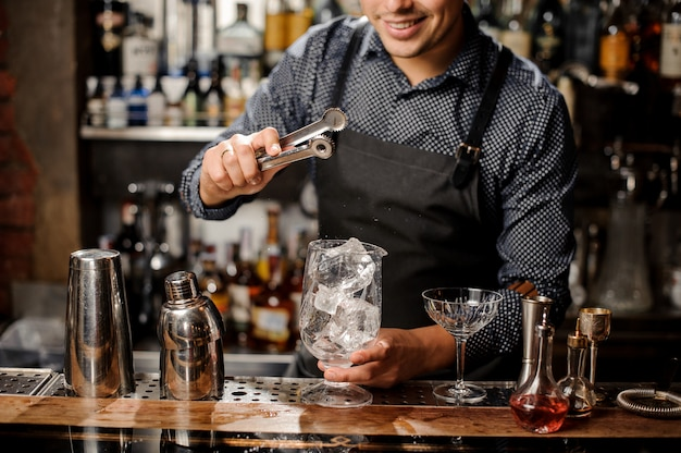 Smiling bartender putting a big ice cube with help of special ice tongs