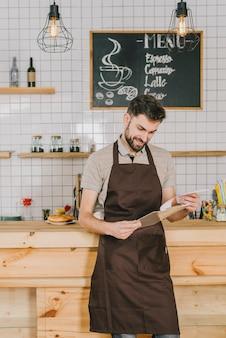 Smiling bartender reading menu