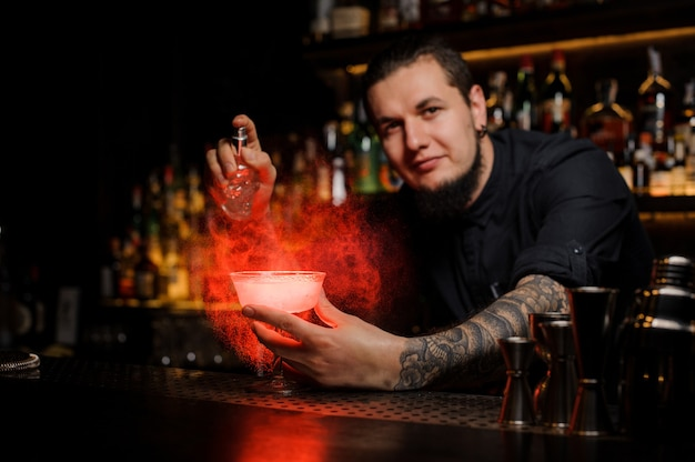Smiling bartender spraying on the delicious cocktail from the special vaporizer on the bar counter